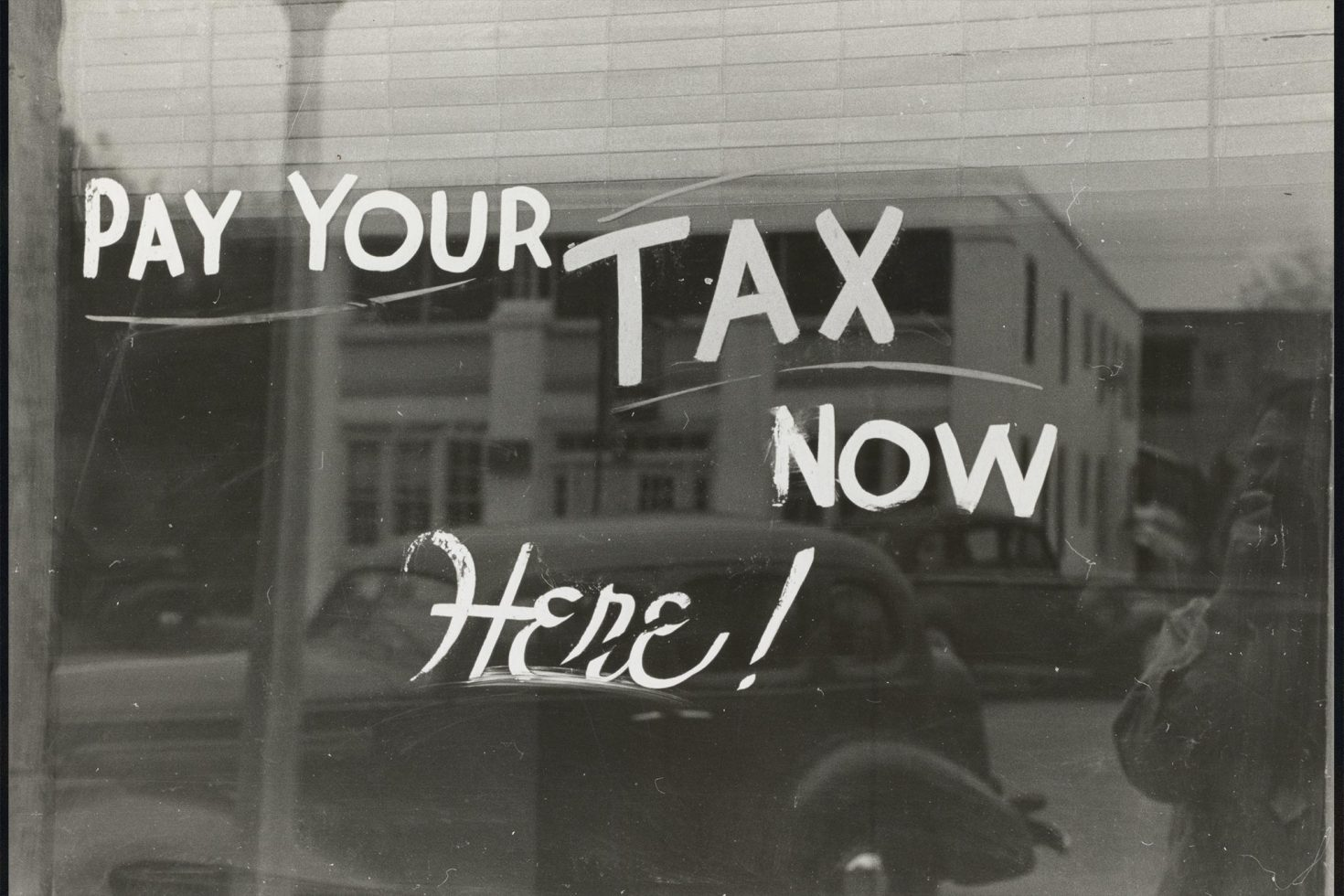Vintage Image of a shop window with 'Pay your tax now Here!' painted on it.